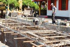 Le travailleur construit le plancher souterrain avec du bâtiment Image libre de droits