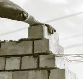Le travailleur construit un mur de briques dans la maison photographie stock