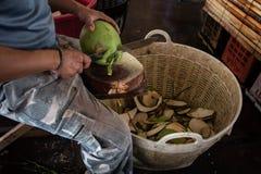 Le travailleur a coupé une noix de coco avec le couteau au marché photos stock