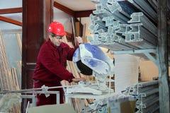 Le travailleur coupant le profil de PVC avec circulaire a vu photographie stock