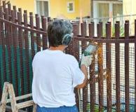 Le travailleur coupe des barres de fer avec la broyeur photographie stock