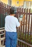 Le travailleur coupe des barres de fer avec la broyeur photo stock