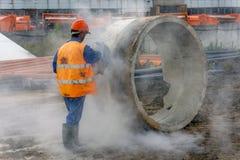 Le travailleur coupe l'anneau concret au chantier de construction photo libre de droits
