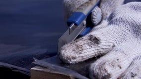 Le travailleur coupe la bâche de toit avec le couteau clip Plan rapproché de travailleur dans les gants avec le revêtement en cao banque de vidéos