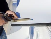 Le travailleur coupe la feuille de PVC avec des ciseaux Photographie stock