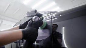 Le travailleur crée un revêtement de protection sur le colorant d'automobile, frottage en tournant la machine de meulage dans l'a clips vidéos