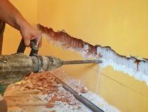Le travailleur démolissent le mur Images stock
