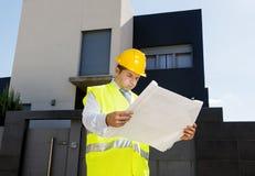 Le travailleur d'agent de maîtrise dans le bâtiment surveillé d'effort blueprints le casque dehors de port de construction Photo libre de droits