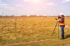 Le travailleur d'arpenteur mesure la distance et la longueur utilisant l'appareil de mesure pour la construction d'un nouveau sec image stock