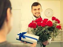 Le travailleur d'homme présente des fleurs photographie stock