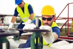Le travailleur d'huile ferme la valve sur l'oléoduc photographie stock libre de droits