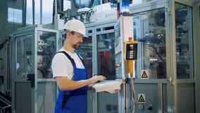 Le travailleur d'usine contrôle un tableau de commande dans l'unité de fabrication banque de vidéos