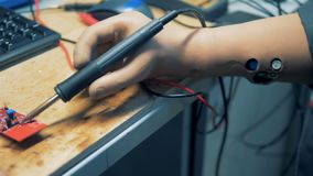 Le travailleur d'usine soude une pièce d'ordinateur avec les mains artificielles 4K clips vidéos
