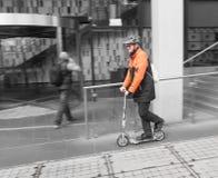 Le travailleur dans la Salut-force permute sur le scooter Photographie stock libre de droits