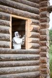 Le travailleur dans les combinaisons et le plein masque protecteur rectifie une ouverture de fenêtre dans une cabane en rondins f photo stock
