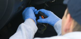 Le travailleur dans les gants bleus répare des électricités de voiture photographie stock