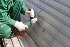 Le travailleur dans uniforme vert et dans des gants de chiffons rectifie la structure métallique ondulée pour rouille de couche d Photos libres de droits