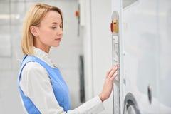 Le travailleur de blanchisserie de fille choisit le programme de lavage photo stock