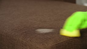 Le travailleur de jeune homme nettoie le sofa dans la chambre ou le bureau banque de vidéos