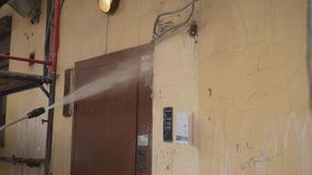 Le travailleur de jeune homme pulvérise l'eau pour loger la façade, porte, lampe, câbles, mur banque de vidéos