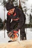 Le travailleur de la construction construit le blockhaus en bois des rondins, utilisant le ch Image libre de droits