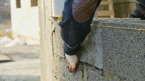 Le travailleur de la construction construit le mur de briques, vue de plan rapproché au chantier de construction photographie stock