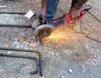 Le travailleur de la construction coupe la scie circulaire de rebar Photos stock