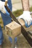 Le travailleur de la construction coupe une scie de main sur un morceau de bois cru Photographie stock
