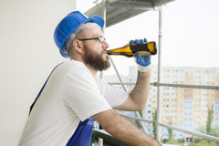 Le travailleur de la construction dans l'usage de travail, les gants protecteurs et un casque sur la tête boit de la bière de la  Photo stock