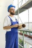 Le travailleur de la construction dans un équipement de travail et dans un casque se tient à une haute altitude sur un chantier d Photos stock