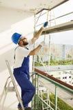 Le travailleur de la construction dans un casque de protection et le travail attire l'échafaudage de mesures sur un chantier de c Images stock