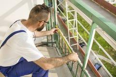 Le travailleur de la construction dans un casque de protection et le travail attire l'échafaudage de mesures sur un chantier de c Images libres de droits