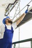 Le travailleur de la construction dans un vêtement de travail, des gants protecteurs et un casque sur la tête donne un marteau Tr Images stock