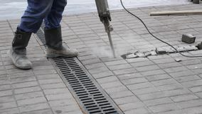 Le travailleur de la construction enlève la tuile en béton avec la foreuse de marteau piqueur dehors clips vidéos