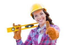 Le travailleur de la construction féminin dans le casque antichoc se tenant de niveau renonce à des pouces photographie stock libre de droits