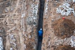 Le travailleur de la construction marche dans le fossé au site Vue sup?rieure photo stock