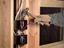 Le travailleur de la construction martèle sur une boîte électrique dans le bâtiment d'une maison photographie stock libre de droits