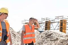 Le travailleur de la construction regardant l'essuyage fatigué de collègue a sué au site photo stock