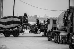 Le travailleur de la construction se tient sur un mélangeur concret sur une photo noire et blanche photographie stock libre de droits