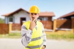 Le travailleur de la construction transformant le regard en mes yeux font des gestes photographie stock