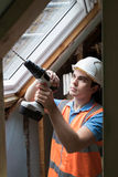 Le travailleur de la construction Using Drill To installent la fenêtre de rechange image stock