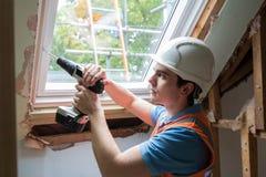 Le travailleur de la construction Using Drill To installent la fenêtre de rechange image libre de droits