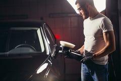 Le travailleur de mécanicien se préparent à la voiture de polissage par la machine d'amortisseur de puissance Image libre de droits