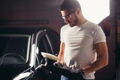 Le travailleur de mécanicien se préparent à la voiture de polissage par la machine d'amortisseur de puissance Photo stock