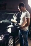 Le travailleur de mécanicien se préparent à la voiture de polissage par la machine d'amortisseur de puissance Images stock