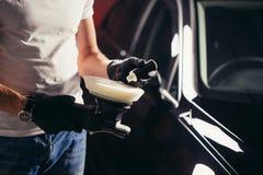 Le travailleur de mécanicien se préparent à la voiture de polissage par la machine d'amortisseur de puissance Images libres de droits