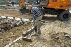 Le travailleur de route balaye le sable entre les pavés ronds Photos stock