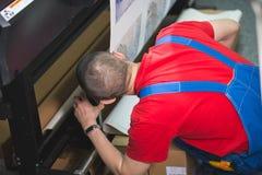 Le travailleur de sexe masculin dans la typographie insère le papier dans la presse typographique photos libres de droits