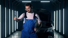 Le travailleur de sexe masculin de garage danse avec des outils et un presse-papiers dans des ses mains banque de vidéos