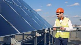 Le travailleur de sexe masculin marche le long des panneaux solaires clips vidéos